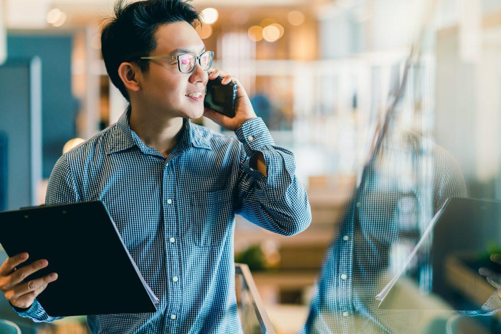 Sempris smart confidence asian startup entrepreneur business owner businessman smile hand use smartphone woking in office background