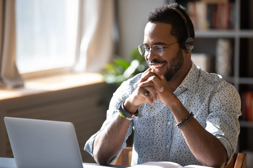 Sempris Happy millennial african american man in glasses wearing headphones, enjoying watching educational webinar on laptop. Smiling young mixed race businessman holding video call with clients partners.